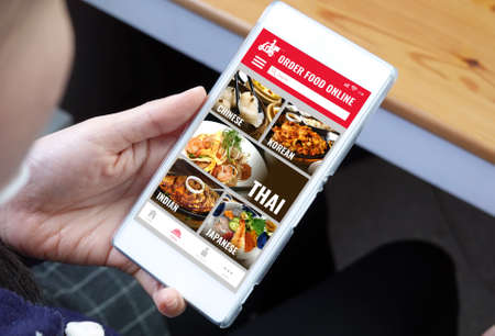 Close-up young woman using smart phone with order food online app 免版税图像 - 155643305