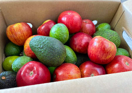 Food delivery box of fresh fruits such as avocado, apple and feijoa