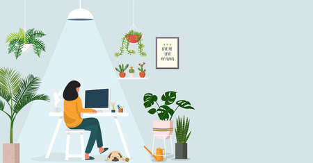 Woman working on laptop at home decorated with indoor plants