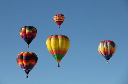 Een groep van kleurrijke heteluchtballonnen tegen een blauwe hemel Genomen op de Albuquerque Balloon Fiesta in New Mexico Stockfoto