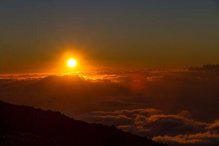 Setting sun above the clouds at Haleakala National Park, Maui, Hawaii