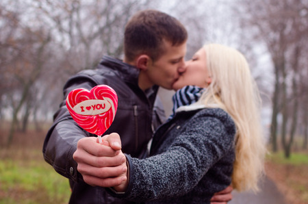 Couple kissing  Holding in hands lollipop written I love you  photo