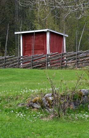 Red and white shed with fence, Sweden photo