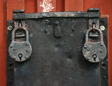 Two old iron padlocks on a lockbox on the wall of a church in Sweden