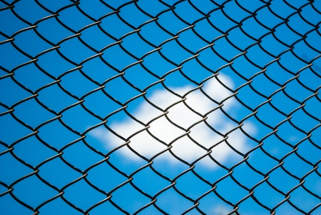 Metal mesh wire fence with blue sky and cluod background photo