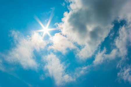 The sun shines bright in the daytime in summer. Blue sky and clouds. Stock Photo - 22952759