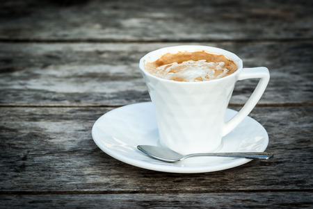 Coffee in a cup on wood background photo
