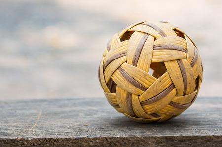 Old Sepak takraw ball put on the wood. Stock Photo - 26379973