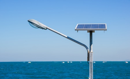 Streetlight with solar panel against sea background photo