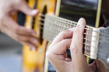Hand playing acoustic guitar, close up Standard-Bild