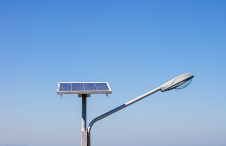 conservation: Streetlight with solar panel on blue sky background Stock Photo