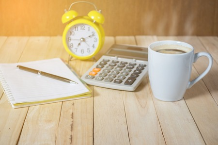 A cup of coffee on the table with calculator and clock.