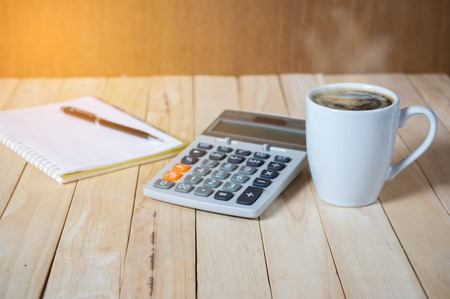 A cup of coffee on the table with calculator and notebook.