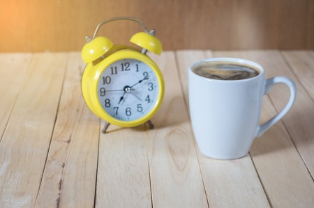 A cup of coffee on the table with  clock. Stock Photo