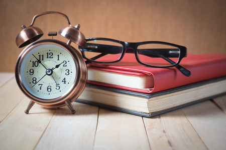 Retro alarm clock and book with glasses.