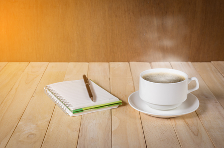 warm cup of coffee on wood background.