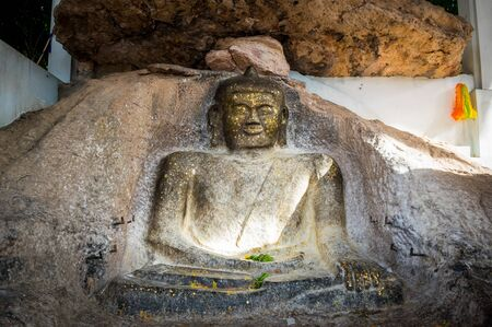Old buddha image on the rock in public Thai temple at Chaiyaphum, Thailand. Standard-Bild