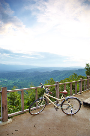 adventuring: yellow bicycle and mountain in sunlight