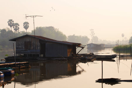 old house boat on river in thailand photo