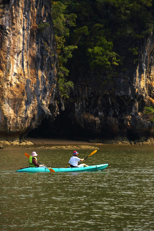 two human on one canoe in thailand photo