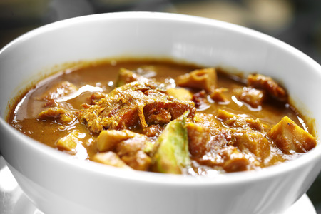 close-up Thaise pittige gele vis curry in witte kom