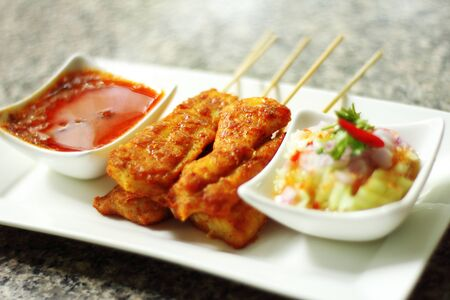asian food: close up yellow indian fish satay in dish