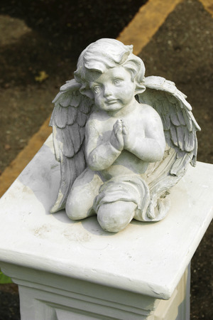 cherub: close up cement cherub doll in garden Stock Photo