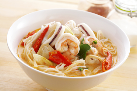 thai noodle: close up thai spicy seafood noodle in ceramic cup Stock Photo