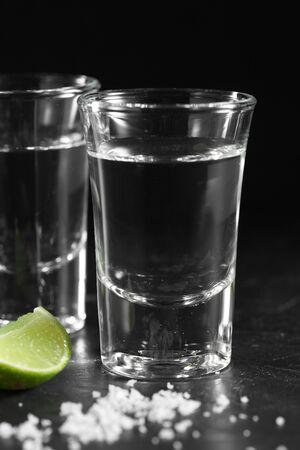 Gros plan de la vodka dans un verre à liqueur sur fond noir, vodka russe au sel et au citron Banque d'images