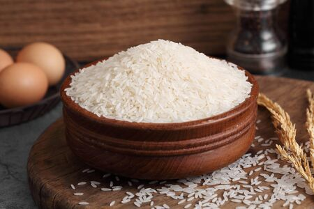 thai white jasmine rice in wooden bowl in kitchen with a blank space for a text, thai agriculture concept