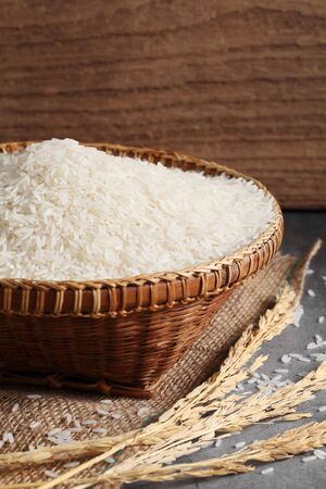 close up thai white jasmine rice in wooden basket in kitchen with a blank space for a text, thai agriculture concept