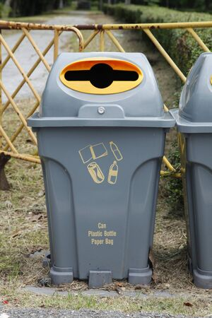 yellow and gray recycle bins with recycle symbol in public park