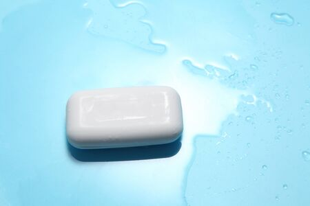white soap and water drop on a blue background with a blank space for a text, shower accessories in top view Stockfoto