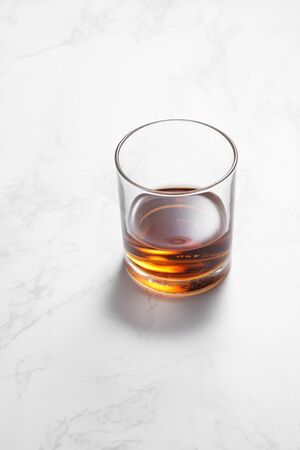 scotch whiskey in glass on a white marble table with a blank space for a text, scotch whiskey in bar background