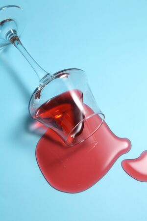 Red wine spilled from glass over blue background with a blank space for a text,  Red wine spilled on color table