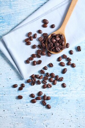 coffee bean and spoon on rustic table with a blank space for a text, coffee bean on blue background