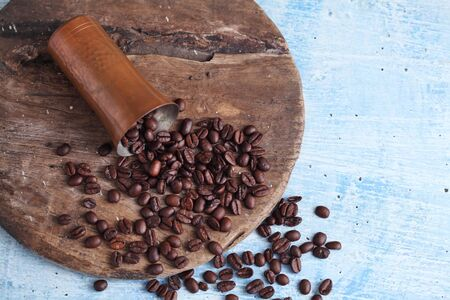 coffee bean and copper cup on rustic table with a blank space for a text, coffee bean on blue background Stockfoto
