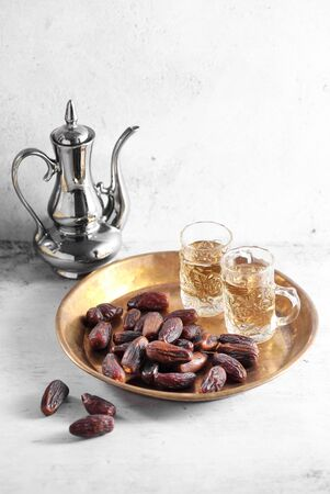 dates fruit and Arab tea on a white concrete background with a blank space for a text, dates fruit on a white background