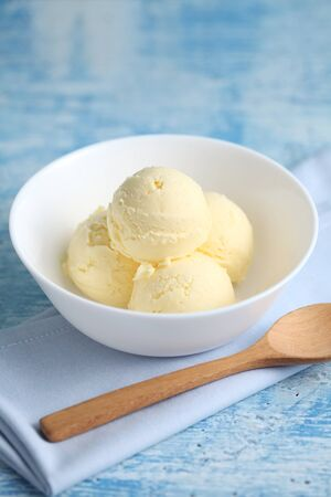 vanilla ice cream on a blue background with a blank space for a text, vanilla ice cream in white ceramic cup