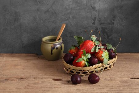 fresh strawberry and cherry in wooden basket with a blank space for a text, Fruit in kitchen background