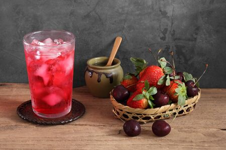 Red cocktail and strawberry and cherry in wooden basket with a blank space for a text, Fruit in kitchen background Stockfoto