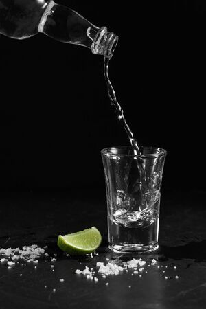 Pouring vodka into the shot glass on a black background with a blank space for a text, Russian vodka with salt and lemon Stockfoto