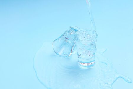pouring vodka to shot glass on blue background with a blank space for a text, Russian vodka on color table Stockfoto