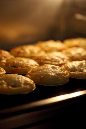 Mini pie from meat and mushrooms baking in industrial oven, Pie and pastry wholesale bakery factory