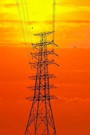 Imagen del polo eléctrico y la silueta puesta de sol.