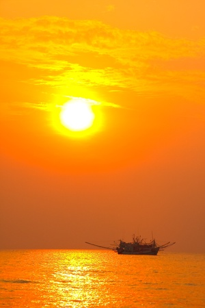 Picture of fishing boat in sunset silhouette. photo