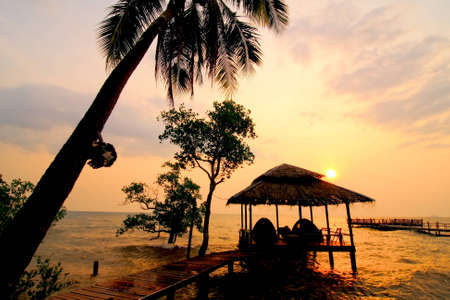 Hut and coconut tree silhouette at sunset, Chang island, Thailand photo