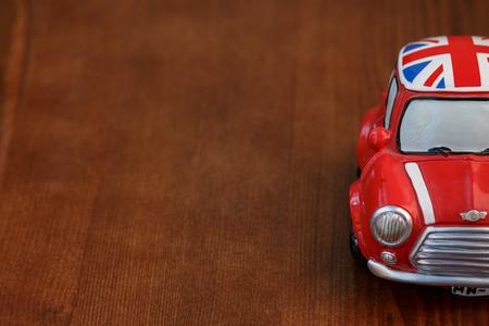 Red Mini Cooper model on wood background