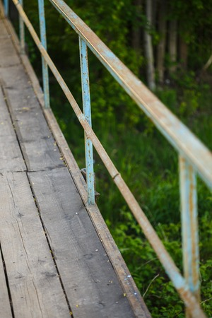 wooden railings: old bridge made of wooden planks with rusty railings