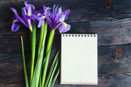 purple irises: bouquet of purple irises on a wooden background with a notebook for your message Stock Photo